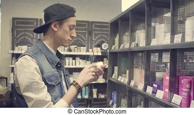 Young man choosing cosmetics in a beauty store
