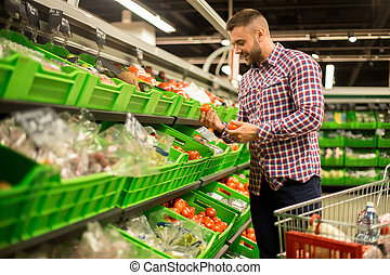 Young Man Choosing Fresh Tomatoes in Supermarket
