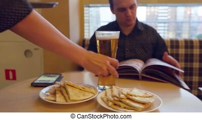 Young man Choosing from a Restaurant Menu  and drinking beer while waiter bring one more beer