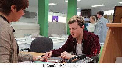 Young Man Choosing Furniture Designs - Young man is...