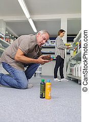 young man choosing household chemicals in supermarket