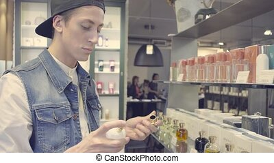 Young man choosing perfume in a beauty store - Portrait of...