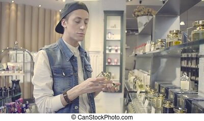 Young man choosing perfume in a beauty store