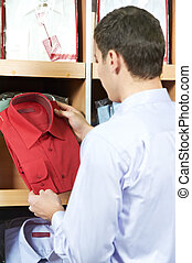 Young man choosing shirt in clothes store