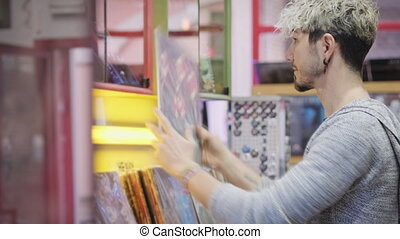 Young Man Choosing Vintage Vinyl LP In Records Shop - Young ...