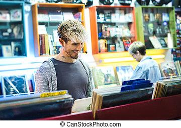Young Man Choosing Vintage Vinyl LP In Records Shop - Young...