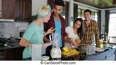 Young Man Chopping Pineapple, Woman Put It In Blender People Group Talking Prepare Healthy Smoothie Two Couples In Kitchen Cooking Together Slow Motion 60