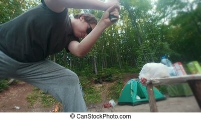Young man chopping wood for the camping bonfire, slow motion