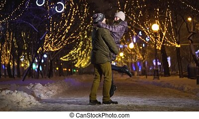 Young man circling his girlfriend in arms - Man whirl his...