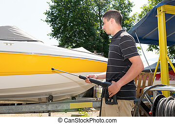 young man cleaning boat with high pressure water