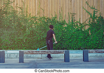 Young man cleaning fountain pool from fallen leaves with net