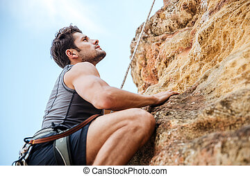 Young man climbing a steep wall in mountain - Young fearless...