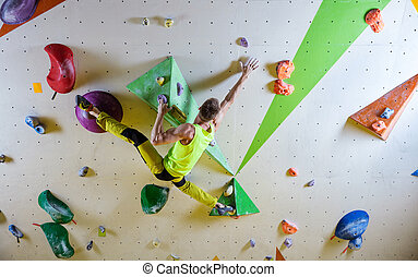 Young man climbing bouldering route, doing splits to reach...