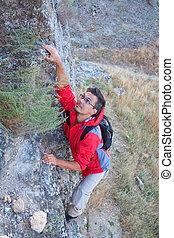 Young man climbing in mountain.