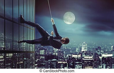 Young man climbing on the skyscraper - Young man climbing on...