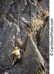 Young Man Climbing Rock - Rear view of young man climbing ...