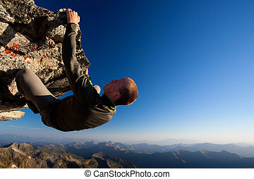 Young man climbing the rock high above mountain range