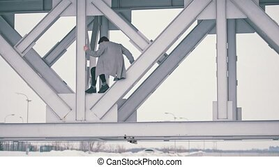 Young man climbing under the bridge in cloudy day, telephoto...
