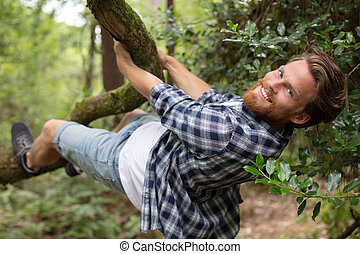 young man clinging to the branch of a tree