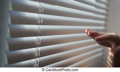 young man close and open is venetian blinds by the window.