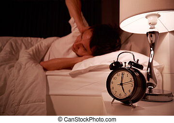 man close his ears by hand from noise of alarm clock on bed
