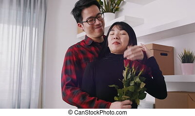 Young man closing eyes of his girlfriend with hand and gifting her with bouquet of red roses on wedding anniversary