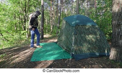 Young man comes to tourist camouflage tent at dawn in the forest. Tourist with long hair takes off his shoes enters in marquee between big trees. Guy enjoys nature on vacation.