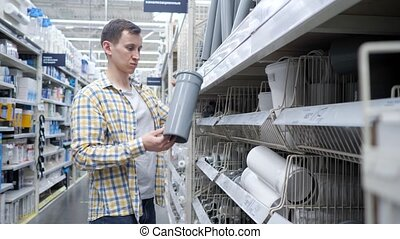 Young man compares sewer pipes in a specialty store.