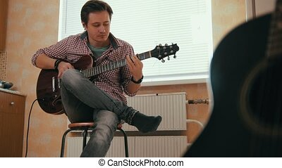Young man composes music on the guitar and plays in the...
