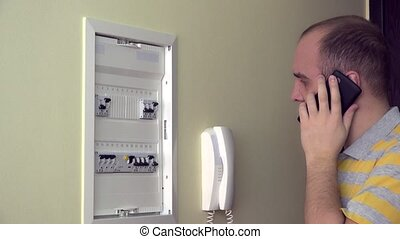 man consults by phone on electrical fault in own room. 4K