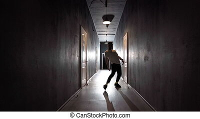 Young man contemporary hip hop dancer dancing in a ray of light in a long dark hallway with lots of white doors on both sides. 4K footage.