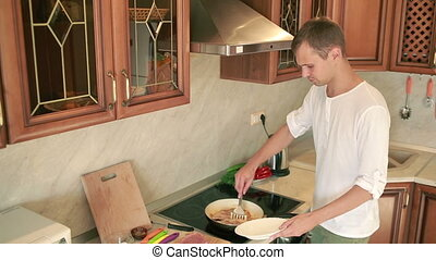 Young man cooking in the kitchen. man preparing meat. Fry in a pan