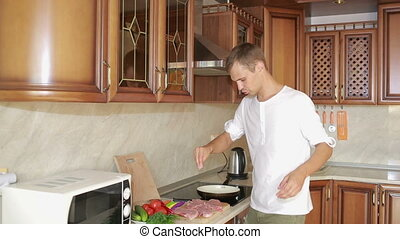Young man cooking in the kitchen. man preparing meat