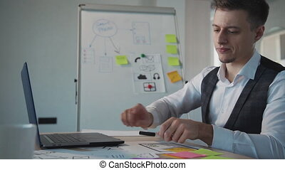 Young man copywriter working with laptop and writing at workspace in agency. Concept create ux design for people. Confident american businessman watching computer screen, taking notes on sticker sitting at desk in office room. Side of manager doing creative work.