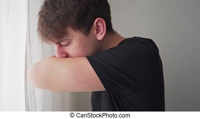 Young man coughing into his arm or elbow to prevent spread ...