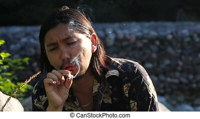 Young man coughing while smoking cigarette, slow motion