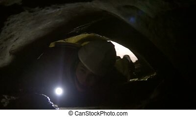 Young man crawls through narrow hole in cave with flashlight...
