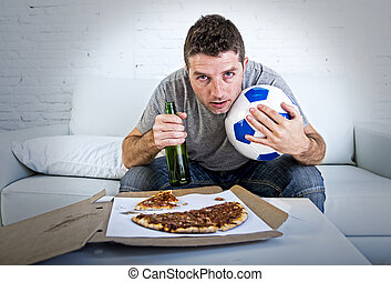 young man crazy anxious and nervous watching football game on television at home couch