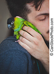 young man cuddle his pet parrot on shoulder