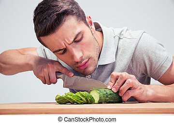 Young man cutting vegetables on the wooden board