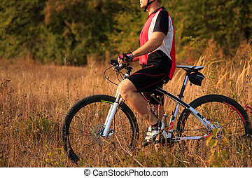 Young man cycling  in the forest