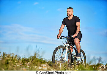 Young man cycling on a green meadow against blue sky with clouds.