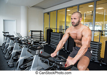 Young  Man Cycling On Bike Bodybuilding Trainer