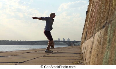 Young Man Dances Rock-N-Roll on a Riverbank With a High Wall in Summer