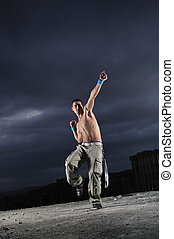 young man dancing and jumping  on top of the building