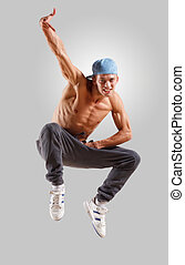 young man dancing hip hop - young man in a blue cap dancing...