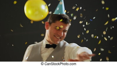 Young man dancing in party hat - Front view close up of a ...