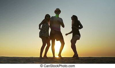 Young man dancing on the beach with two women at sunrise
