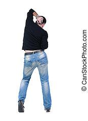 Young man dancing. Rear view.