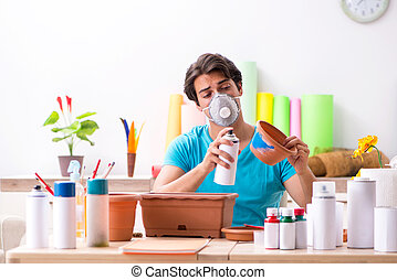 Young man decorating pottery in class